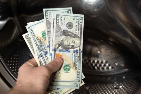 Concept - money laundering. Washing machine and dollar bills.