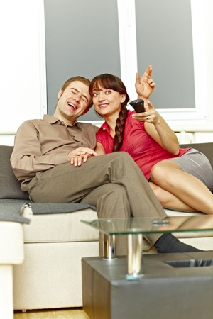 Nice couple watching tv at home and laughing