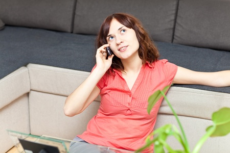 Nice young adult talking the phone sitting on the floor near the table and green plants