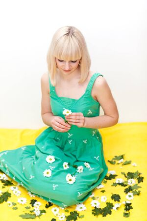 Nice young adult sitting on yellow floor with flowers in her hands and around her
