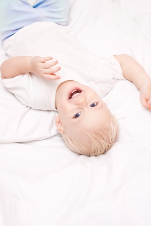 Cute little boy lying on white sheets in the bed and laughing Stock Photo