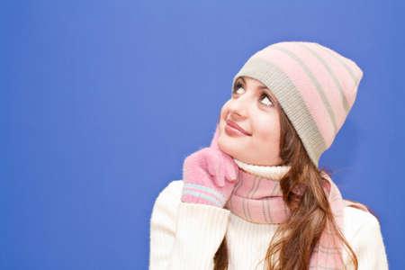 Nice dressed girl looking upward on blue background