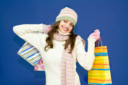 Young woman in hat and scarf holding colorful shopping bags on blue background Stock Photo