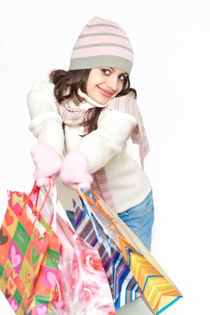Young woman in hat and scarf holding colorful shopping bags isolated