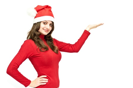 Christmas girl in red santa hat pointing with her hand isolated on white Stock Photo