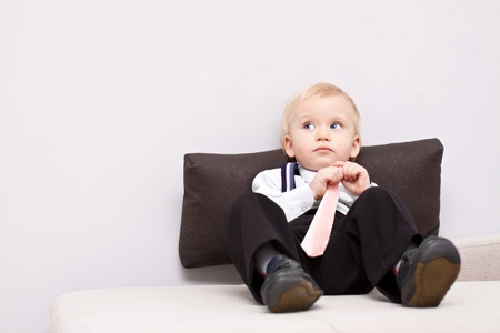 Little tired businessman sitting on the sofa and get some rest Stock Photo