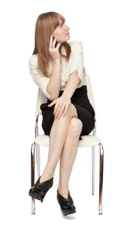 Businesswoman sitting on chair and talking by phone over isolated background Stock Photo