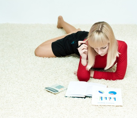 Nice looking girl planing budget on the floor with calculator and sheets