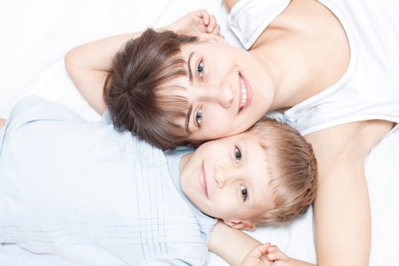 Happy mother and son lying on the bed and smiling Stock Photo