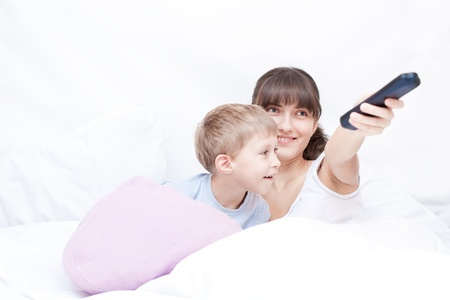 Mother with remote control and son lying on the bed and watching TV Stock Photo