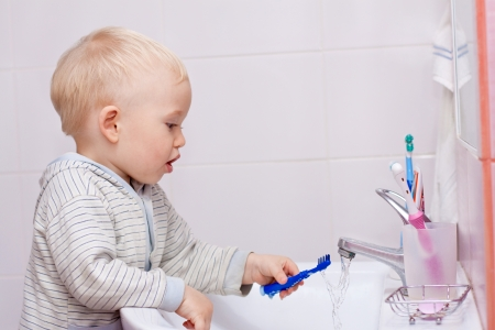 Cute little boy cleaning his teeth in the bathroom