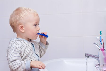 Cute little boy cleaning his teeth in the bathroom