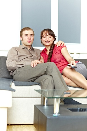 Nice couple watching tv at home