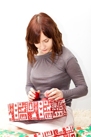 Young lady open boxes with presents