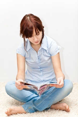 Young adult sitting on the floor with magazine