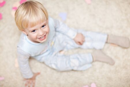 Sweet little kid sitting on floor Stock Photo