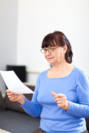 Senior woman reading something on paper