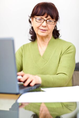 Senior woman sitting at the table Stock Photo
