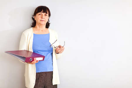 Senior woman with folder standing at the wall