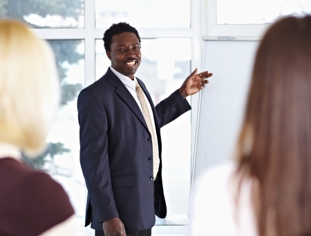 African American male speaker giving a presentation at business meeting Stock Photo