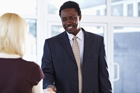 African American business man and caucasian woman shaking hands Stock Photo - 9067864