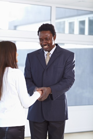 African American business man and caucasian woman shaking hands Stock Photo