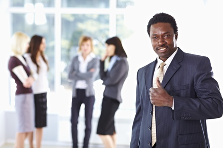 Successful African Amercian businessman with colleagues in the background Stock Photo