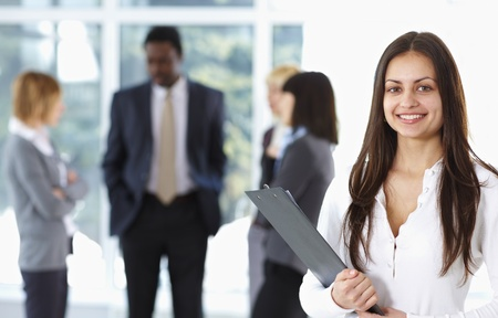 Happy cute businesswoman with colleagues in the background Stock Photo