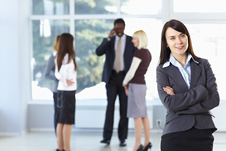 Happy cute businesswoman with colleagues in the background Stock Photo - 9067855