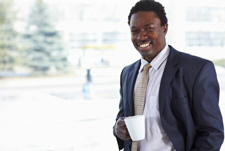 African American business man with cup at the window Stock Photo - 9067862