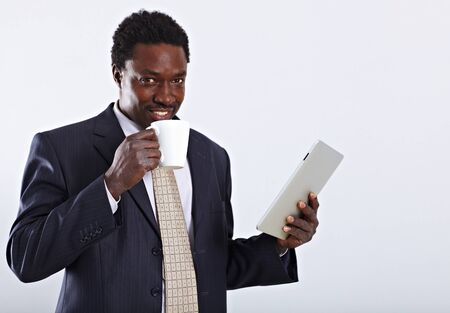 Handsome African American business man with cup of tea and tablet pc Stock Photo