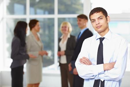 imagen corporativa: Hombre de negocios de j�venes felices con compa�eros de equipo discutiendo en segundo plano