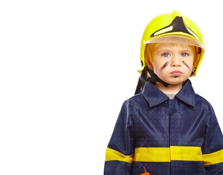 Serious little boy in fireman costume isolated on white photo