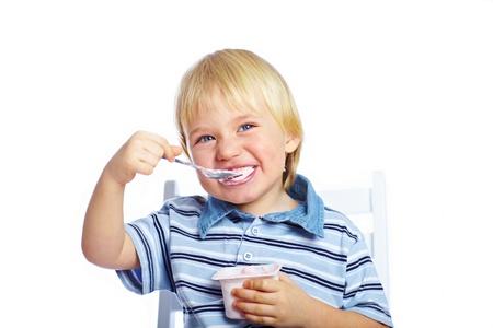 Little boy eating yogurt isolated on white background Stock Photo