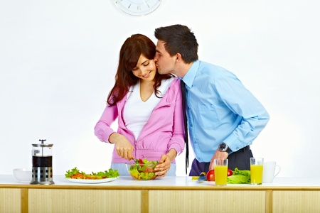 Beautiful wife is preparing some food for lunch and her husband is kissing her in her cheek photo