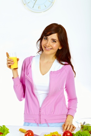 Portrait of beautiful woman standing in the kitchen with glass of orange juice and smiling Stock Photo