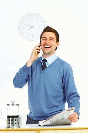 Businessman with newspaper in kitchen talking by cell phone and laughing Stock Photo