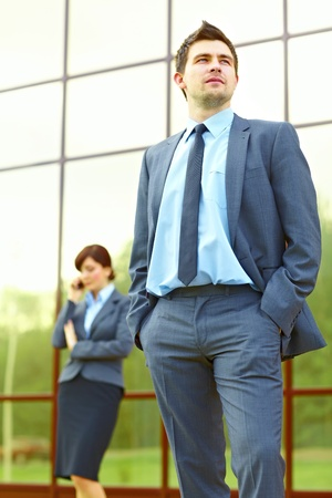 Businessman posing in front of business building and businesswoman in the background talking on the phone