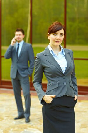 Businesswoman posing in front of business building and businessman in the background talking on the phone