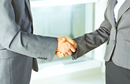 Businessman shaking hands with businesswoman at the office Stock Photo