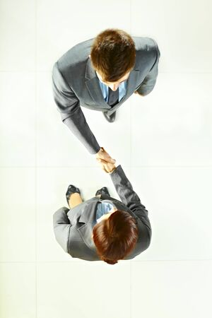 woman on top: Businessman shake hands with businesswoman standing on the floor top view