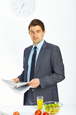 Portrait of businessman holding newspaper in the kitchen Stock Photo