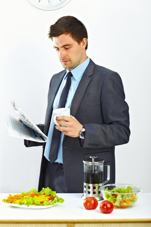 Businessman with cup of coffee reading newspaper in the kitchen