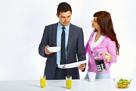 Business man reading newspaper in the kitchen before go to work and his wife holding kettle with coffee near him