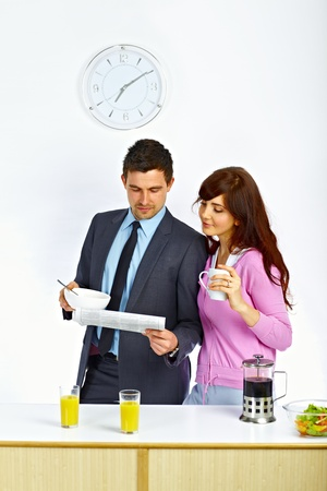 Businessman reading newspaper with his wife in kitchen before go to work