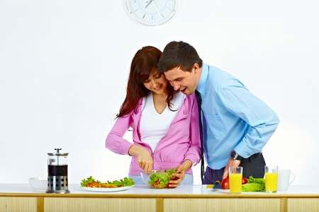 Beautiful couple preparing a salad for lunch in the kitchen