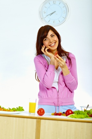 Portrait of tender woman standing in kitchen on talking on the phone Stock Photo