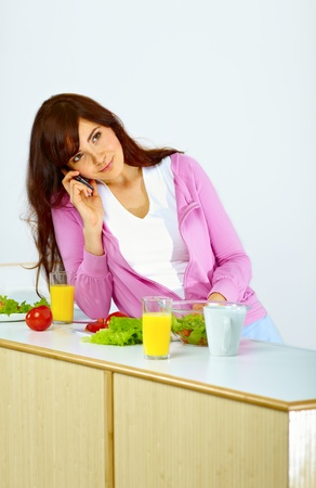 Portrait of beautiful woman standing in kitchen on talking on the phone
