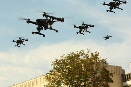 Swarm of Unmanned Aircraft System (UAV) Quadcopters Drones In The Air Over City