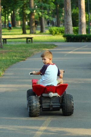 Boy riding big red toy car in park, back view